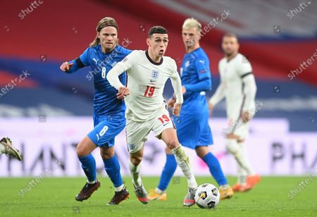 England's Phil Foden, center, and Iceland's Birkir Bjarnason challenge for the ball during the UEFA Nations League soccer match between England and Iceland at Wembley stadium in London
