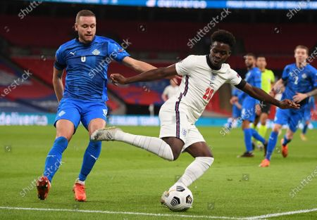 England's Bukayo Saka, right, and Iceland's Sverrir Ingason challenge for the ball during the UEFA Nations League soccer match between England and Iceland at Wembley stadium in London