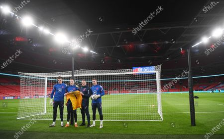 England goalkeepers (L-R) Nick Pope, Jordan Pickford, goalkeeper coach Martyn Margetson, and Dean Henderson hold a tribute jersey in memory of former England goalkeeper Ray Clemence, who died on 15 November, ahead of the UEFA Nations League soccer match between England and Iceland in London, Britain, 18 November 2020.