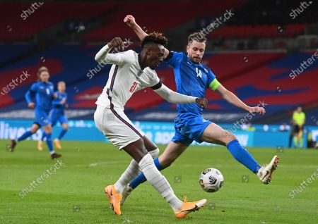 Stock Image of England's Tammy Abraham, left, shoots the ball as Iceland's Kari Arnason, right, tries to stop him, during the UEFA Nations League soccer match between England and Iceland at Wembley stadium in London, . Engalnd won the match 4-0