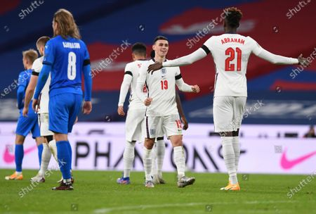 England's Phil Foden, center, celebrates with teammate Tammy Abraham after scoring his team's fourth goal during the UEFA Nations League soccer match between England and Iceland at Wembley stadium in London, . England won the match 4-0