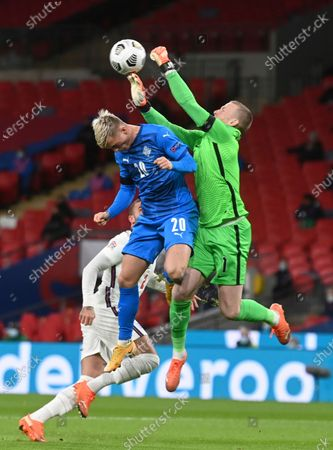 Iceland's Albert Gudmundsson, left, fights fopr the ball with England's goalkeeper Jordan Pickford, right, during the UEFA Nations League soccer match between England and Iceland at Wembley stadium in London