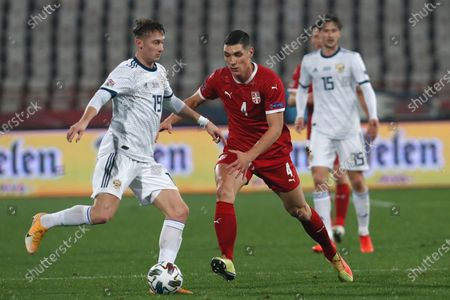 Stock Image of Russia's Aleksandr Sobolev, left, challenges for the ball with Russia's Ilya Kutepov during the UEFA Nations League soccer match between Serbia and Russia at the Rajko Mitic Stadium, in Belgrade, Serbia