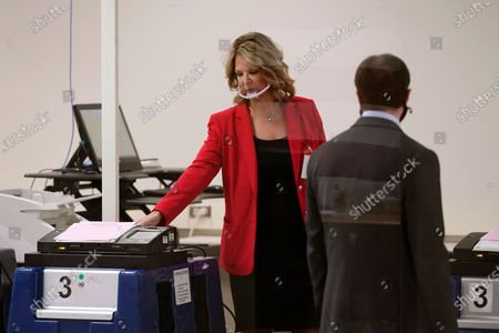 Dr. Kelli Ward, left, chair of the Republican Party of Arizona, looks at test ballots as she talks with Scott Jarrett, right, Maricopa County Elections Department Director of Election Day and Emergency Voting, at the Maricopa County Elections Department prior to the conducting of a post-election logic and accuracy test for the general election, in Phoenix