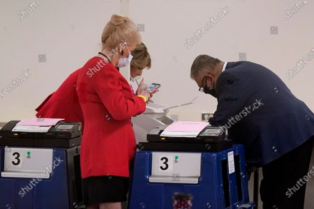 Linda Brickman, front left, vice chair of the Maricopa County Republicans, Dr. Kelli Ward, back left, chair of the Arizona Republican Party, talk with Rey Valenzuela, right, Maricopa County Elections Department Director of Early Voting and Election Services, as the department conducts a post-election logic and accuracy test for the general election, in Phoenix