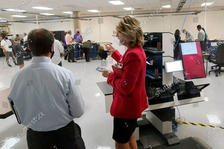 Stock Photo of Kelli Ward, right, chair of the Republican Party of Arizona, talks with Scott Jarrett, Maricopa County Elections Department director of Election Day and Emergency Voting, at the Maricopa County Elections Department during the post-election logic and accuracy test for the general election, in Phoenix