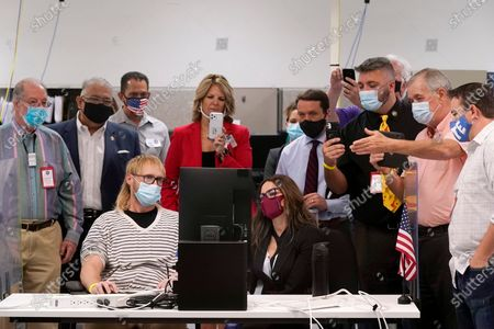 Arizona election staff, other state officials and election observers from the political parties, including Dr. Kelli Ward, top middle, chair of the Arizona Republican Party, and Steven Slugocki, far right, chair of the Maricopa County Democratic Party, participate in a ballot adjudication test on a computer screen as the Maricopa County Elections Department conducts a post-election logic and accuracy test for the general election, in Phoenix
