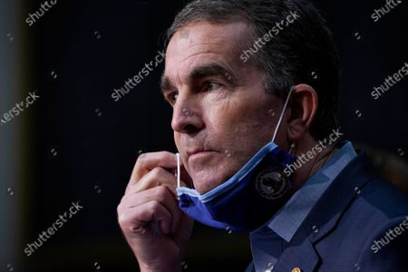 Virginia Gov. Ralph Northam removes his mask to answer a question during a COVID-19 briefing at the Capitol in Richmond, Va