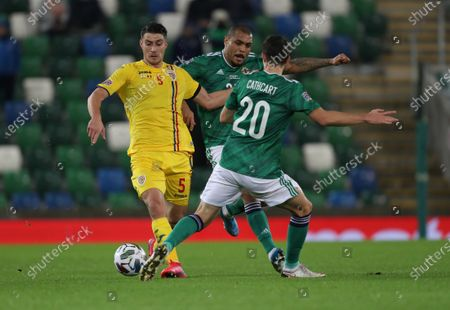 Northern Ireland's Josh Magennis and Craig Cathcart and Romania's Ionut Nedelcearu