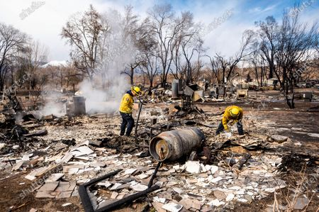 Firefighters Emiliano Saldivar, left, and Chris Martinez sift through debris to recover keepsakes for residents after the Mountain View Fire tore though the Walker community in Mono County, Calif