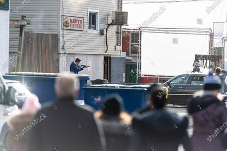 Stock Photo of Actor Pierson Fode holds a prop firearm as local onlookers watch the scene being directed