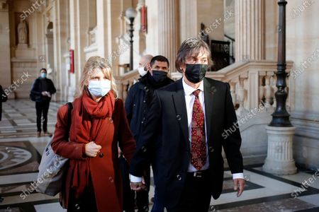 French-American Mark Moogalian, right, and his wife Isabelle arrive at the Thalys attack trial, at the Paris courthouse, . The lawyer for an American who was scheduled to testify about his role in the dramatic capture of an Islamic State operative aboard a high-speed train says his witness has been hospitalized after he flew in to Paris