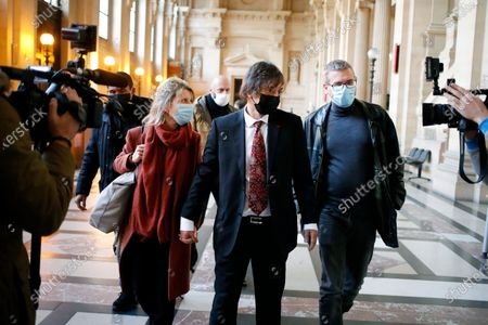 French-American Mark Moogalian, center, his wife Isabelle, left, and his lawyer Thibault de Montbrial, right, arrive at the Thalys attack trial, at the Paris courthouse, . The lawyer for an American who was scheduled to testify about his role in the dramatic capture of an Islamic State operative aboard a high-speed train says his witness has been hospitalized after he flew in to Paris