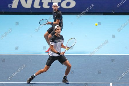 Lukasz Kubot of Poland and Marcelo Melo of Brazil return to Wesley Koolhof of the Netherlands and Nikola Mektic of Croatia during their doubles tennis match at the ATP World Finals tennis tournament at the O2 arena in London