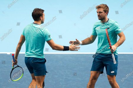 Kevin Krawietz of Germany and Andreas Mies of Germany clasp hands after winning a point against Rajeev Ram of the United States and Joe Salisbury of Britain during their doubles tennis match at the ATP World Finals tennis tournament at the O2 arena in London