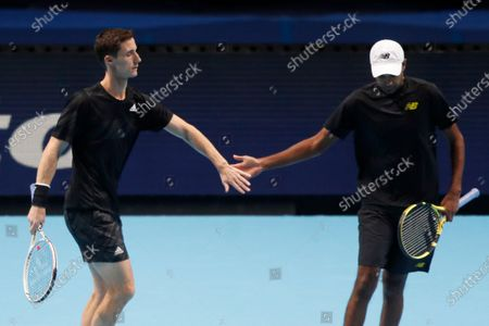 Rajeev Ram of the United States and Joe Salisbury of Britain, left, touch hands during their tennis match against Kevin Krawietz of Germany and Andreas Mies of Germany at the ATP World Finals tennis tournament at the O2 arena in London