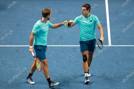 Kevin Krawietz of Germany and Andreas Mies of Germany touch fists after winning a point against Rajeev Ram of the United States and Joe Salisbury of Britain during their doubles tennis match at the ATP World Finals tennis tournament at the O2 arena in London