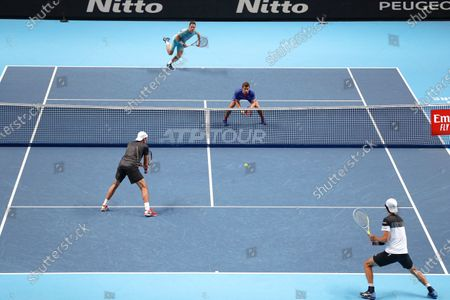 Stock Photo of Wesley Koolhof of the Netherlands and Nikola Mektic of Croatia serve to Lukasz Kubot of Poland and Marcelo Melo of Brazil during their doubles tennis match at the ATP World Finals tennis tournament at the O2 arena in London