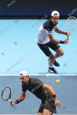 Stock Image of Lukasz Kubot of Poland and Marcelo Melo of Brazil return to Wesley Koolhof of the Netherlands and Nikola Mektic of Croatia during their doubles tennis match at the ATP World Finals tennis tournament at the O2 arena in London