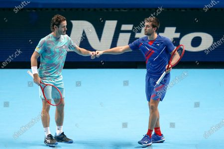 Wesley Koolhof of the Netherlands and Nikola Mektic of Croatia touch fists during their doubles tennis match against Lukasz Kubot of Poland and Marcelo Melo of Brazil at the ATP World Finals tennis tournament at the O2 arena in London