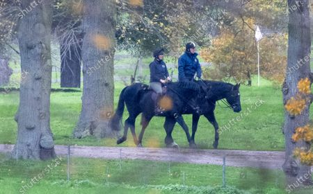 Prince Andrew out riding with a groom in the grounds of Windsor Castle.