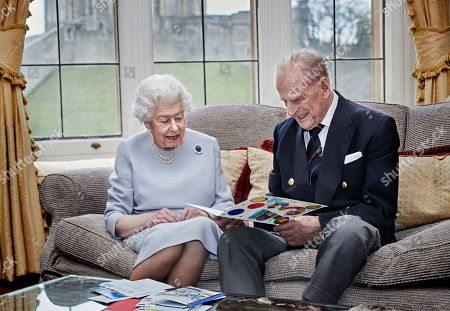 Queen Elizabeth II and Prince Philip, Prince Philip look at their homemade wedding anniversary card, given to them by their great grandchildren Prince George, Princess Charlotte and Prince Louis, in the Oak Room at Windsor Castle ahead of their 73rd wedding anniversary
