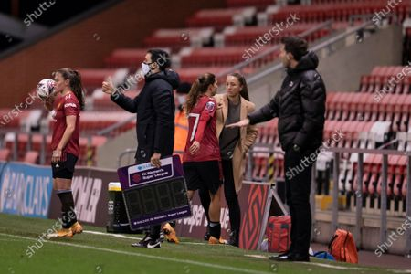 Manchester United Women manager Casey Stoney centre right is seen with Tobin Heath after the latter's substitution
