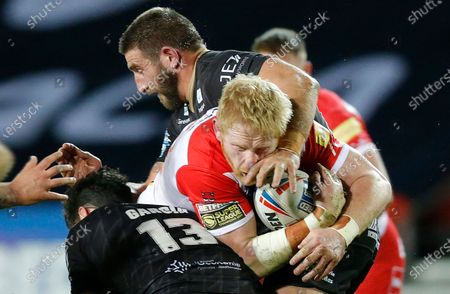 James Graham of St Helens tries to pass Benjamin Garcia of Catalans Dragons and Julian Bousquet of Catalans Dragons