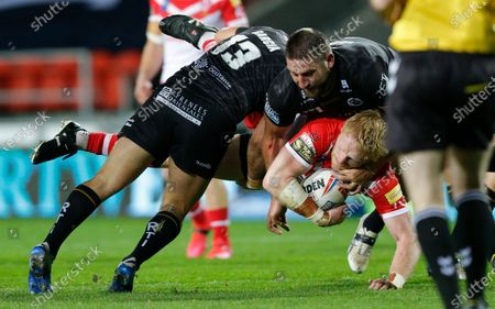 James Graham of St Helens is airborne by Benjamin Garcia of Catalans Dragons and Julian Bousquet of Catalans Dragons