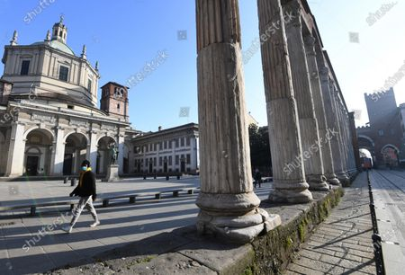Stock Photo of A man wearing a face mask walks by the Columns of San Lorenzo, an ancient construction of the late Roman period in Milan located in front of the basilica of the same name near the Porta Ticinese, in Milan, Italy, 19 November 2020. The President of European Central Bank (ECB), Christine Lagarde, when speaking to the ECON commission of the EU Parliament, reported that in general the economy of the euro zone will severely be affected by the consequences of the rapid increase in coronavirus infections and the restoration of containment measures, posing clearly downside risks to perspectives.