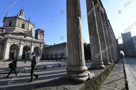 Stock Image of A man wearing a face mask walks by the Columns of San Lorenzo, an ancient construction of the late Roman period in Milan located in front of the basilica of the same name near the Porta Ticinese, in Milan, Italy, 19 November 2020. The President of European Central Bank (ECB), Christine Lagarde, when speaking to the ECON commission of the EU Parliament, reported that in general the economy of the euro zone will severely be affected by the consequences of the rapid increase in coronavirus infections and the restoration of containment measures, posing clearly downside risks to perspectives.