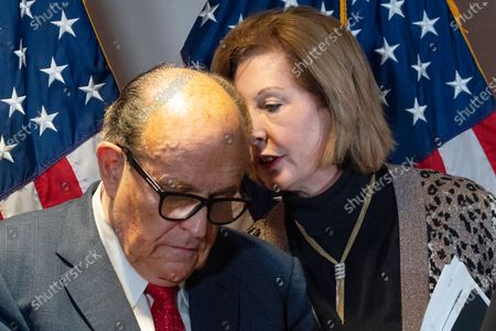 Former Mayor of New York Rudy Giuliani, left, listens to Sidney Powell, both lawyers for President Donald Trump, during a news conference at the Republican National Committee headquarters, in Washington