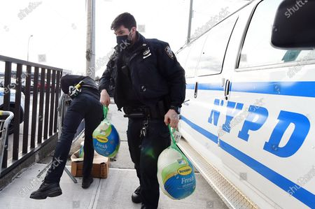 NYPD officers load turkeys in preparation for the 113th Precinct Turkey Giveaway