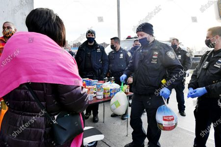 NYPD officers hand out turkeys and food for the 113th Precinct Turkey Giveaway
