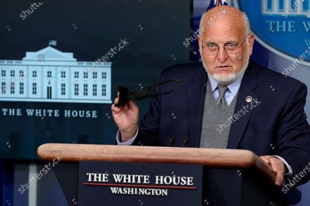 Centers for Disease Control and Prevention Director Dr. Robert Redfield holds a face mask as he speaks during a news conference with the coronavirus task force at the White House in Washington