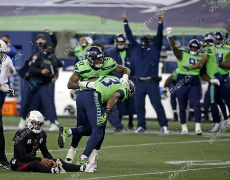Seattle Seahawks defensive end Carlos Dunlap (43) celebrates with defensive end L.J. Collier (91) after Dunlap sacked Arizona Cardinals quarterback Kyler Murray, left, late in the second half of an NFL football game, in Seattle. The Seahawks won 28-21
