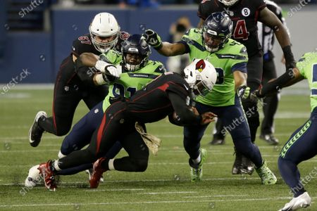Arizona Cardinals quarterback Kyler Murray, center, is tackled by Seattle Seahawks defensive ends L.J. Collier (91) and Carlos Dunlap (43) during the first half of an NFL football game, in Seattle