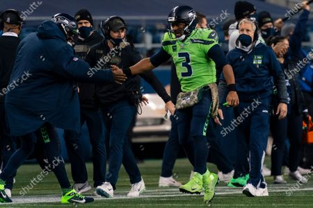 Seattle Seahawks quarterback Russell Wilson (3) is congratulated by quarterback Geno Smith, left, after a touchdown during the first half an NFL football game against the Arizona Cardinals, in Seattle. The Seahawks won 28-21