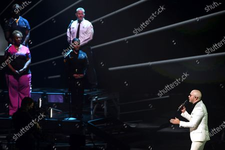 Stock Picture of Pitbull, right, performs along with frontline workers as his band for the 21st Latin Grammy Awards, airing, at American Airlines Arena in Miami