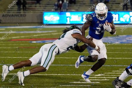 Tulsa running back Corey Taylor II, right, avoids a tackle by Tulane linebacker Dorian Williams during the first overtime of an NCAA college football game in Tulsa, Okla