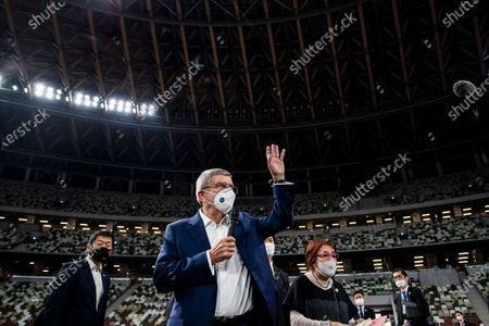 "IOC President Thomas Bach wearing a face mask waves as he speaks to the media at the National Stadium, the main venue for the 2020 Olympic and Paralympic Games postponed until July 2021 due to the coronavirus pandemic, in Tokyo . Bach said during this week's trip to Tokyo that he is ""encouraging"" all Olympic ""participants"" and fans to be vaccinated - if one becomes available - if they are going to attend next year's Tokyo Olympics"