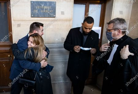 A Thalys train employee hugs US citizens Alek Skarlatos, as Anthony Sadler puts on his face mask and French lawyer Thibault de Montbrial looks on (R), outside the court room during the fifth day of the Thalys attack trial, in Paris, France, 20 November 2020. On 21 August 2015, gunman Ayoub El-Khazzani opened fire with an assault rifle, shot and wounded three people on a Thalys train travelling between Amsterdam and Paris before the assailant was overpowered by passengers.The incident happened near Arras in northern France shortly after 1600 GMT and the gunman was arrested when the train stopped at the town's station.