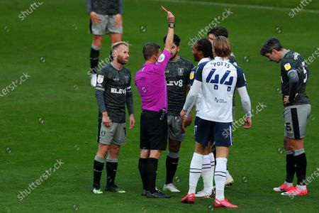 Referee David Webb shows Josh Windass of Sheffield Wednesday a re card for his challenge on Joe Rafferty of Preston North End
