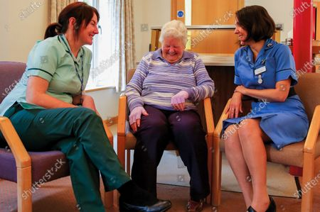 Stock Picture of Staff with patient at Robert Horrell Mac Millan Day Therapy Centre, 2015. A paramedic has spent more than 40 years photographing the changing face of the NHS - and published his pictures in a new book. Amateur photographer Chris Porsz, 67, spent many of his days off over the last four decades accompanying colleagues to capture the patient's journey from the 999 call to the hospital. He has taken hundreds of pictures of doctors, nurses, patients and wards at three hospitals in Peterborough, Cambridgeshire and now produced a book, Just Be Kind, with part proceeds going to Breast Cancer Research.Chris took dozens of photos over the years, whilst working as a porter and later a paramedic, and his pictures offer a unique behind-the-scenes view of the NHS from the 1980s, with nurses neatly dressed in blue gingham and frilly hats, to the present with masked doctors dealing with the coronavirus pandemic.