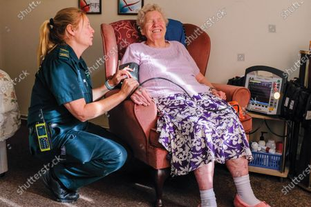 Chris Porsz crewmate Rachel Gouws attends patient at home Peterborough, October 2019. A paramedic has spent more than 40 years photographing the changing face of the NHS - and published his pictures in a new book. Amateur photographer Chris Porsz, 67, spent many of his days off over the last four decades accompanying colleagues to capture the patient's journey from the 999 call to the hospital. He has taken hundreds of pictures of doctors, nurses, patients and wards at three hospitals in Peterborough, Cambridgeshire and now produced a book, Just Be Kind, with part proceeds going to Breast Cancer Research.Chris took dozens of photos over the years, whilst working as a porter and later a paramedic, and his pictures offer a unique behind-the-scenes view of the NHS from the 1980s, with nurses neatly dressed in blue gingham and frilly hats, to the present with masked doctors dealing with the coronavirus pandemic.