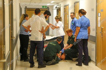 Stock Image of Patient collapses in ED corridor Peterborough City Hospital, August 2015. A paramedic has spent more than 40 years photographing the changing face of the NHS - and published his pictures in a new book. Amateur photographer Chris Porsz, 67, spent many of his days off over the last four decades accompanying colleagues to capture the patient's journey from the 999 call to the hospital. He has taken hundreds of pictures of doctors, nurses, patients and wards at three hospitals in Peterborough, Cambridgeshire and now produced a book, Just Be Kind, with part proceeds going to Breast Cancer Research.Chris took dozens of photos over the years, whilst working as a porter and later a paramedic, and his pictures offer a unique behind-the-scenes view of the NHS from the 1980s, with nurses neatly dressed in blue gingham and frilly hats, to the present with masked doctors dealing with the coronavirus pandemic.