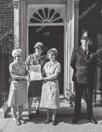 Local nurses hand in a petition from the people of Peterborough. Nurses (L-R): Karen Todd, Sharon Jackson, Diane, 10 Downing Street 1982. A paramedic has spent more than 40 years photographing the changing face of the NHS - and published his pictures in a new book. Amateur photographer Chris Porsz, 67, spent many of his days off over the last four decades accompanying colleagues to capture the patient's journey from the 999 call to the hospital. He has taken hundreds of pictures of doctors, nurses, patients and wards at three hospitals in Peterborough, Cambridgeshire and now produced a book, Just Be Kind, with part proceeds going to Breast Cancer Research.Chris took dozens of photos over the years, whilst working as a porter and later a paramedic, and his pictures offer a unique behind-the-scenes view of the NHS from the 1980s, with nurses neatly dressed in blue gingham and frilly hats, to the present with masked doctors dealing with the coronavirus pandemic.