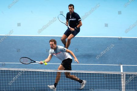 Stock Picture of Mate Pavic of Croatia, behind, and Bruno Soares of Brazil, front, play a return to John Peers of Australia and Michael Venus of New Zealand during their doubles tennis match against at the ATP World Finals tennis tournament at the O2 arena in London