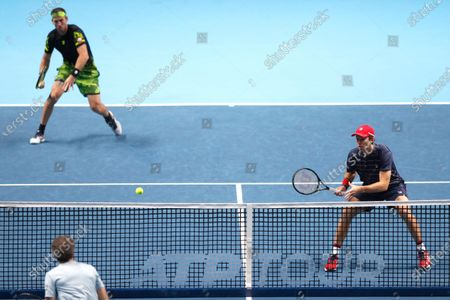 John Peers of Australia, right, and Michael Venus of New Zealand, left, play a return during their doubles tennis match against Mate Pavic of Croatia and Bruno Soares of Brazil at the ATP World Finals tennis tournament at the O2 arena in London