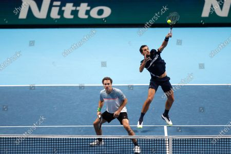 Mate Pavic of Croatia, right, and Bruno Soares of Brazil, left, play a return to John Peers of Australia and Michael Venus of New Zealand during their doubles tennis match at the ATP World Finals tennis tournament at the O2 arena in London